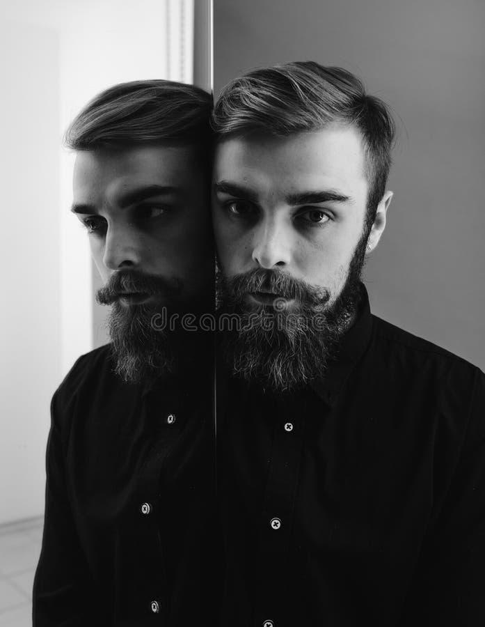 De zwart-witte foto van een mens met een baard en een modieus kapsel kleedde zich in het zwarte overhemd die zich naast de spiege royalty-vrije stock afbeeldingen