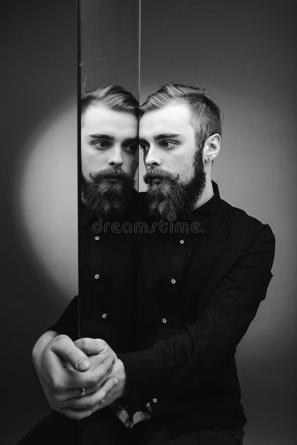 De zwart-witte foto van een mens met een baard en een modieus kapsel kleedde zich in het zwarte overhemd die zich naast de spiege stock fotografie