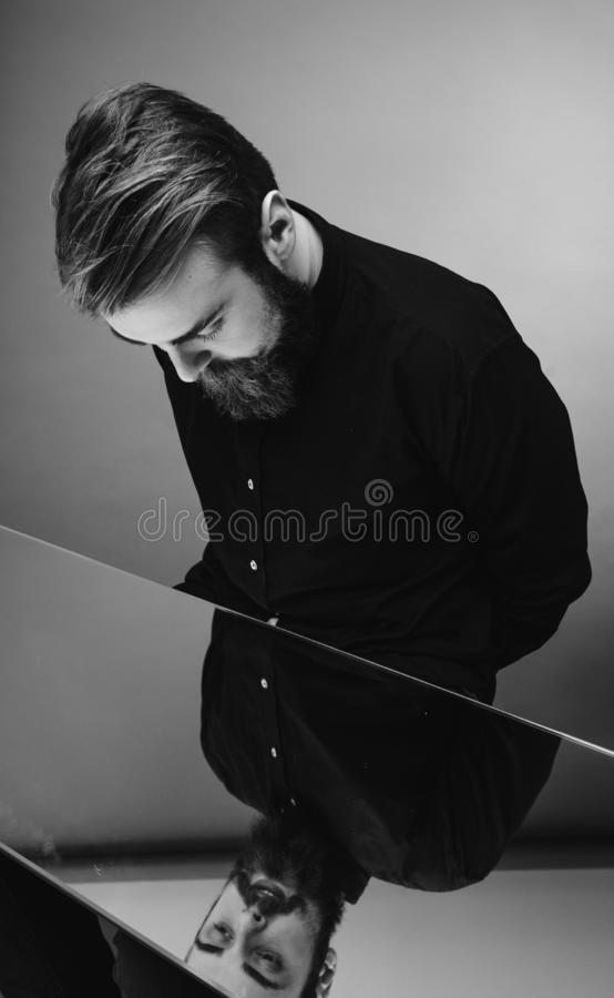 De zwart-witte foto van een mens met een baard en een modieus kapsel kleedde zich in het zwarte overhemd die zich over de spiegel royalty-vrije stock foto's