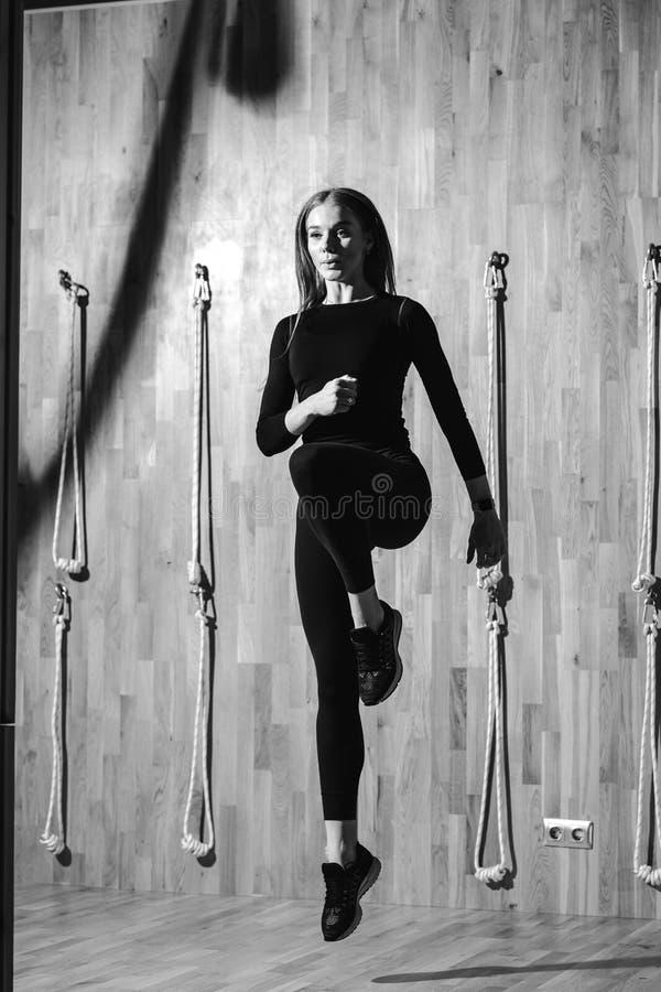 De zwart-witte foto van een slank meisje gekleed in een zwarte sportkleding springt naast het kabelmateriaal in royalty-vrije stock foto's