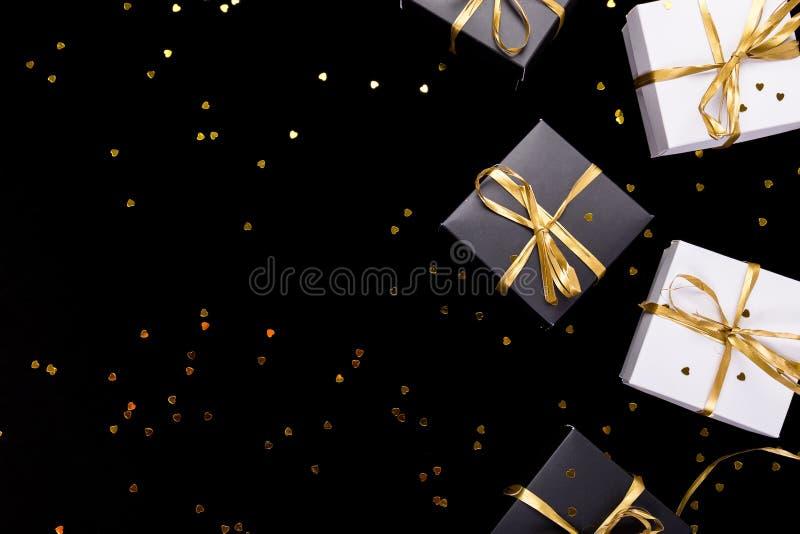 De zwart-witte giftdozen met gouden lint glanzen achtergrond Vlak leg De ruimte van het exemplaar royalty-vrije stock afbeelding
