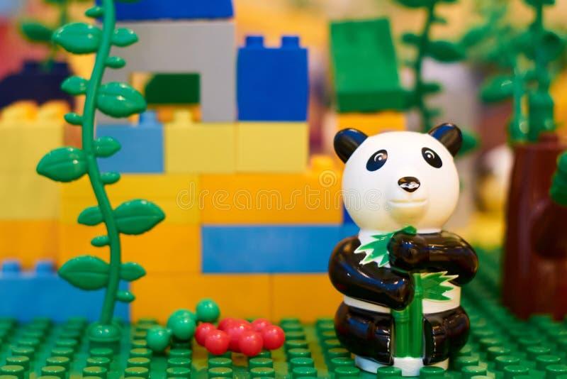 De zwart-witte panda zit alleen tegen de achtergrond van kubussen van de ontwerper stock foto's