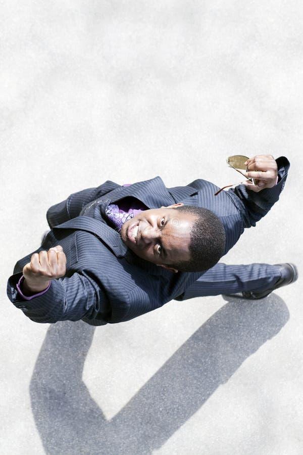 De zwarte bedrijfsmens heft zijn vuisten in triomf op royalty-vrije stock foto