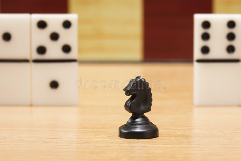 De zwarte close-up van het schaakpaard op een achtergrond van domino's en een spel schepen in royalty-vrije stock foto's