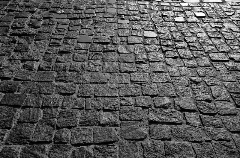 De zwarte cobbled de achtergrond van de steenweg met weerspiegeling van licht op de weg wordt gezien die De zwarte of donkere gri stock foto