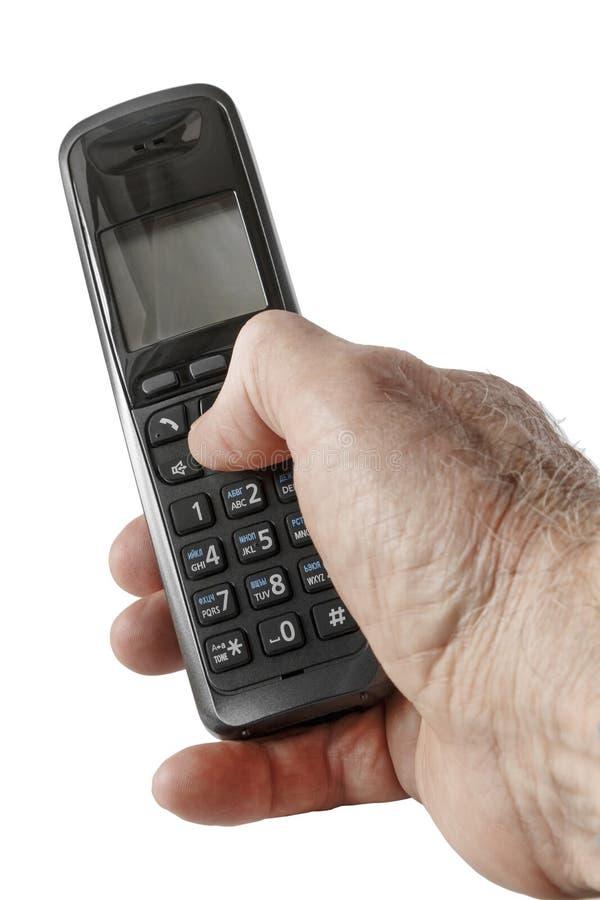 De zwarte draadloze telefoon in een hand stock afbeelding