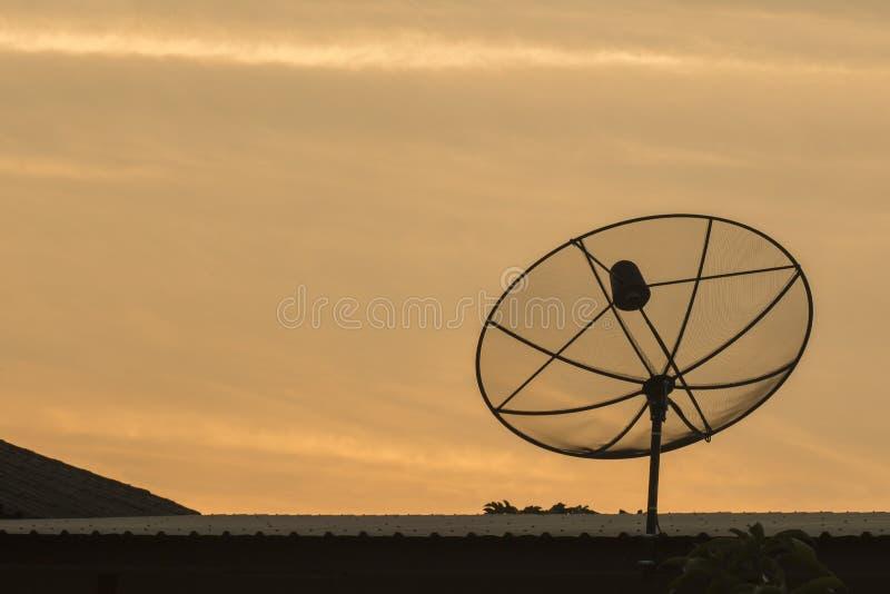 De zwarte en donkere satellietachtergrond van de schotelshemel gokd op dak stock foto
