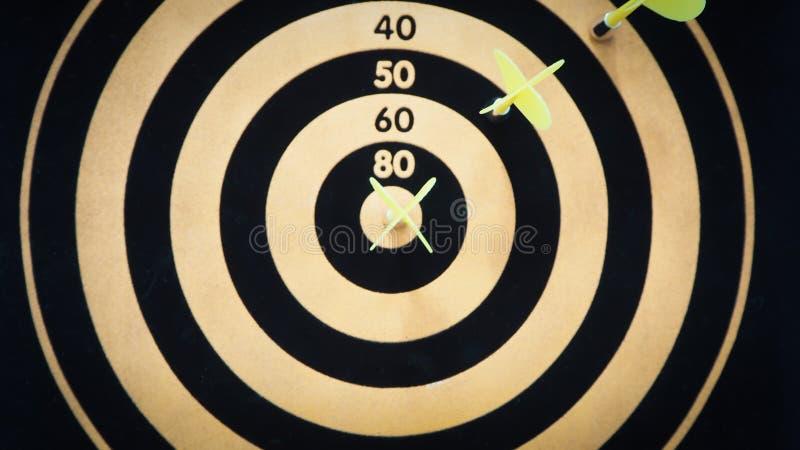 De zwarte en gele pijl die van het bullseyepijltje doelcentrum van dartboard raakt Concept succes, doel, doel, voltooiing selecti stock afbeeldingen