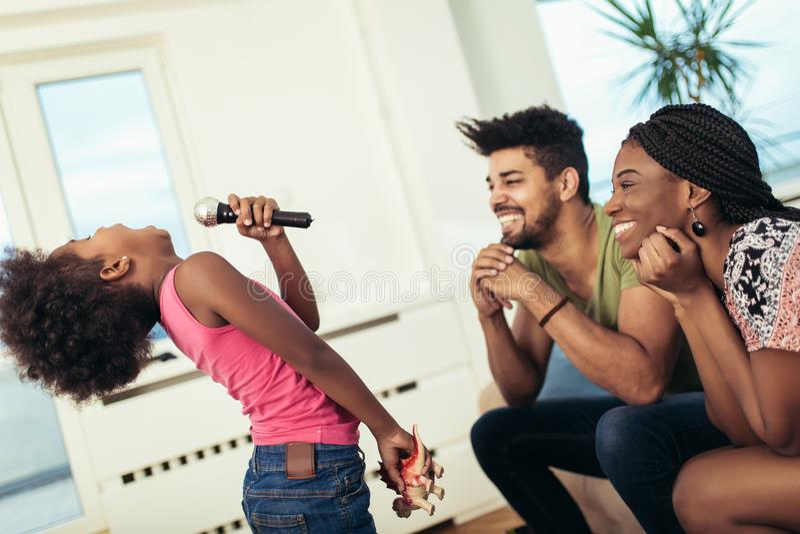De zwarte familie geniet van zingend karaoke stock fotografie