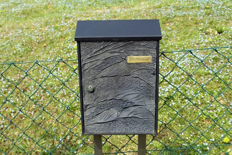 De zwarte gesneden brievenbus met de lente bloeit achtergrond royalty-vrije stock afbeeldingen