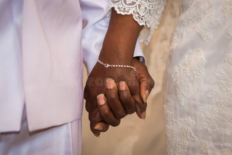 De zwarte handen van de paarholding tijdens huwelijk stock foto