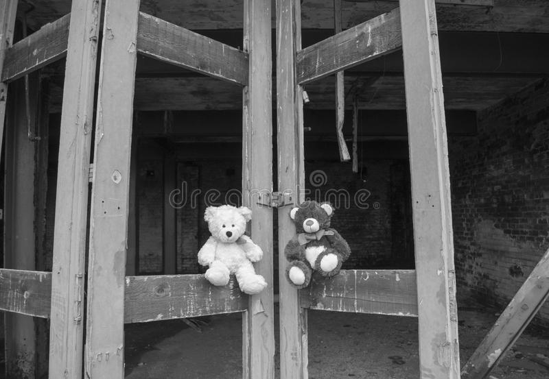 De Zwarte & het Wit van Teddy Bears Sitting On Derelict Fie Station Bay Doors In stock afbeeldingen