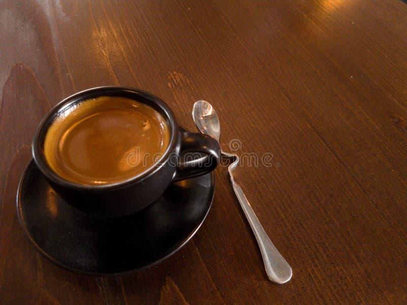 De zwarte de koffiemokken en lepel worden geplaatst op bruin hout royalty-vrije stock afbeelding