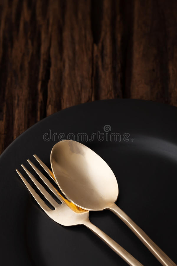 De zwarte lege lepel van de plaatvork op houten lijstachtergrond royalty-vrije stock foto