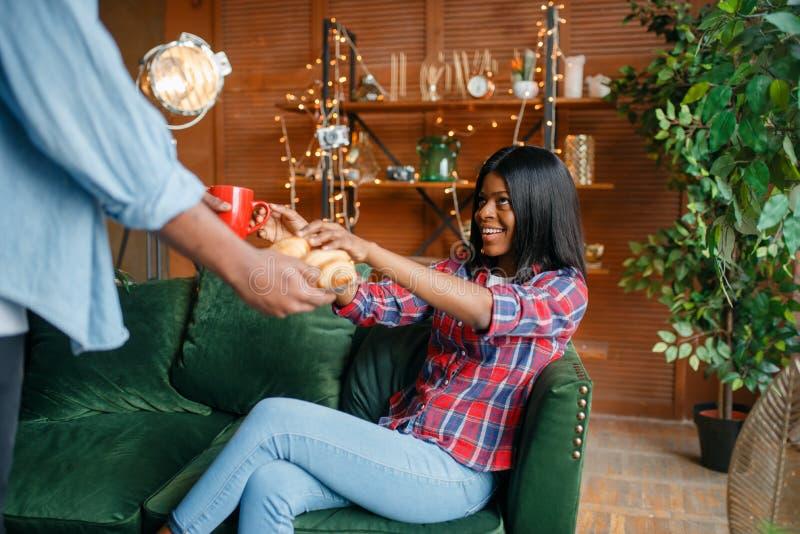 De zwarte man brengt koffie en bakkerij aan zijn vrouw royalty-vrije stock fotografie