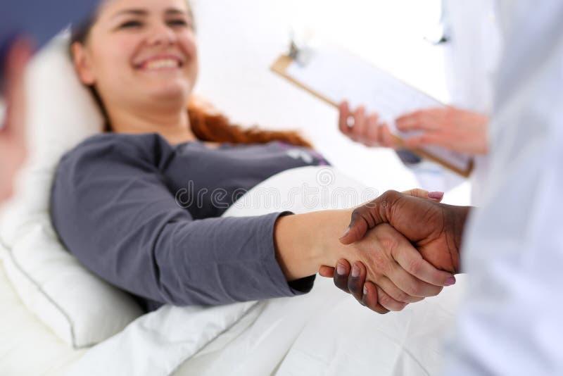 De zwarte mannelijke handen van de artsenschok zoals hello met vrouwelijke patiënt royalty-vrije stock foto