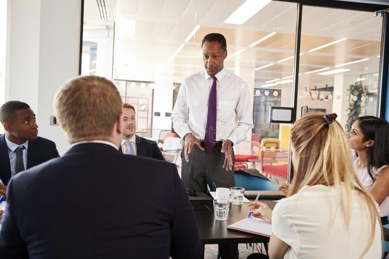 De zwarte mannelijke manager bevindt zich sprekend op een commerciële vergadering royalty-vrije stock afbeeldingen