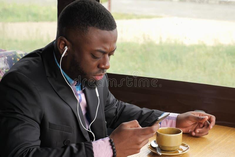 De zwarte mens is het luisteren muziek in oortelefoons doorbladerend smartphonezitting in koffie royalty-vrije stock foto's