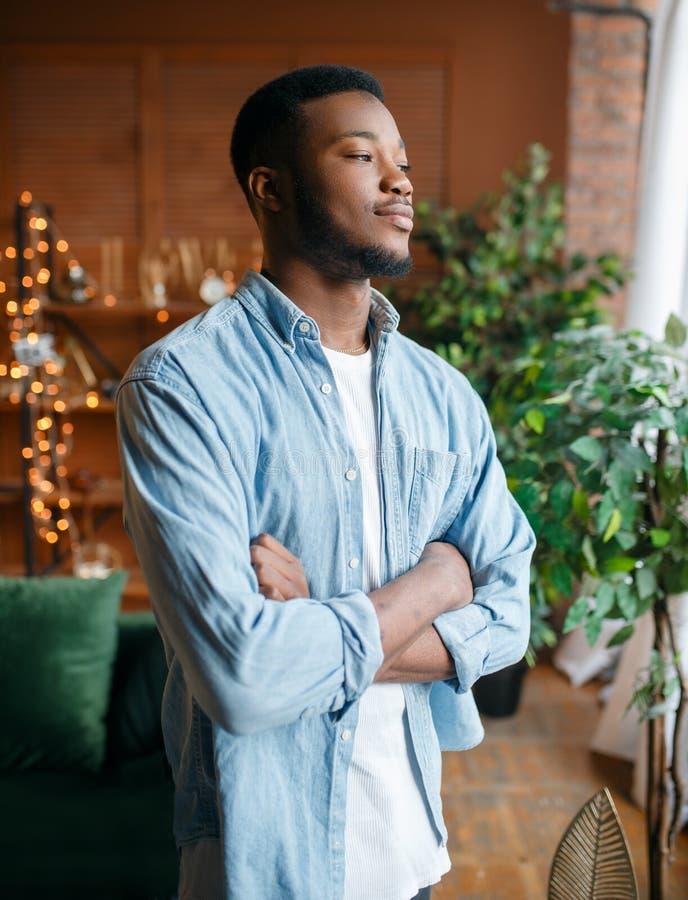 De zwarte mens met een sluwheid kijkt in de woonkamer royalty-vrije stock foto