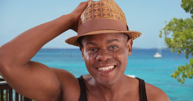 De zwarte mens stelt gelukkig voor een portret door het strand royalty-vrije stock afbeeldingen