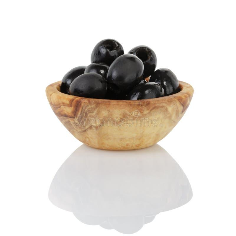 De zwarte olijven van kunnen in houten werpen stock afbeelding