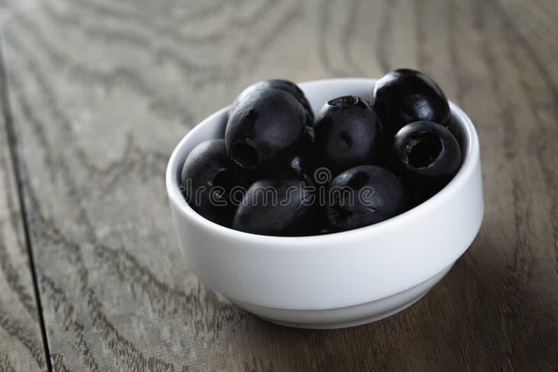 De zwarte olijven van kunnen in kom op lijst stock afbeelding