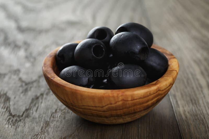 De zwarte olijven van kunnen in kom op lijst royalty-vrije stock afbeeldingen