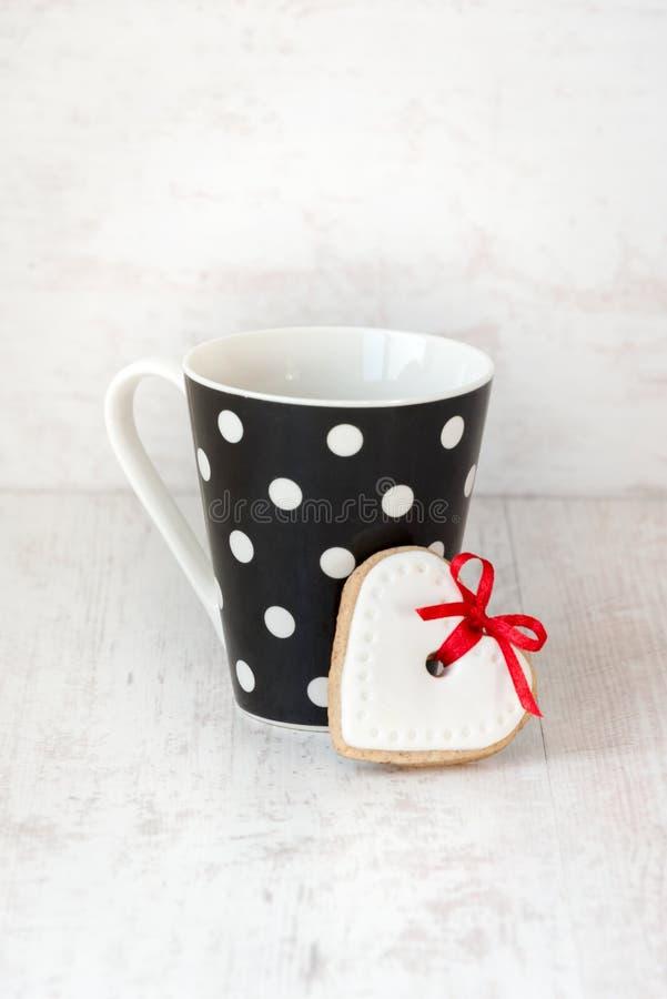 De zwarte polka stippelde koffiekop met een hart gevormd eigengemaakt koekje over witte houten achtergrond royalty-vrije stock fotografie