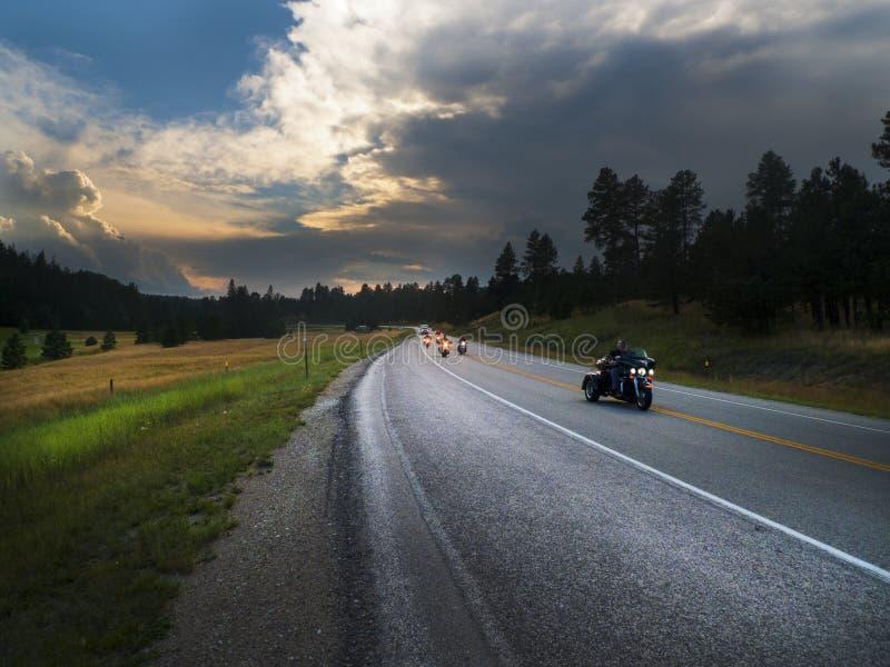 De zwarte rit van Heuvelsmotorrijders bij zonsondergang stock fotografie