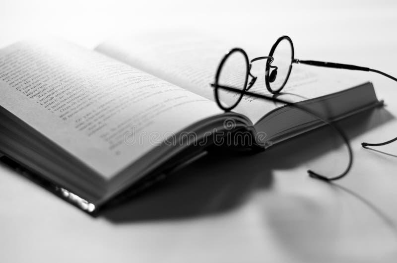 De zwarte Ronde de oude glazen legt op een open wit boek, dat op een witte achtergrond ligt royalty-vrije stock afbeeldingen