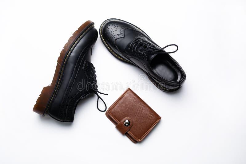 De zwarte schoenen van de leerderby met polyurethaanzolen en een bruine beurs met een knoop op een witte achtergrond stock afbeeldingen