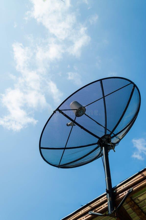 De zwarte schotel van de antennecommunicatiesatelliet over zonnige blauwe hemel stock fotografie