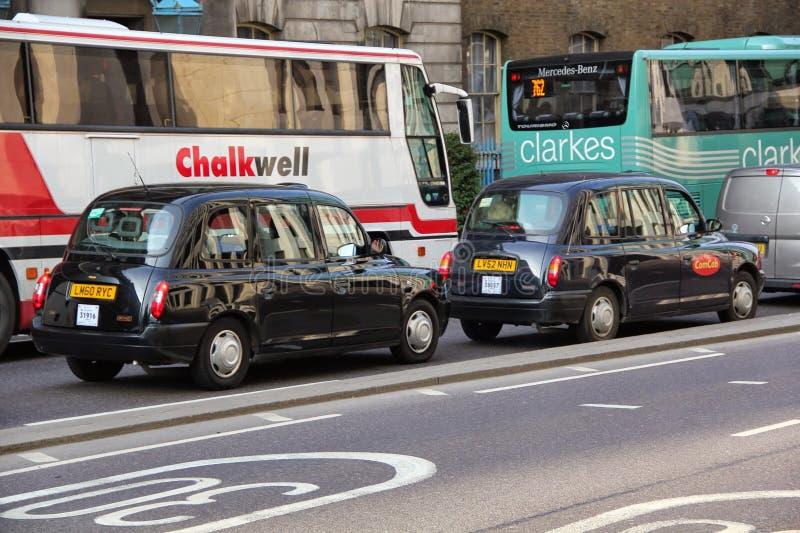 De zwarte taxi die van Londen elkaar voor de bussen op de weg volgen stock foto's