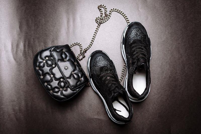 De zwarte tennisschoenen op een witte dikke zool verfraaiden met zwarte fonkelingen en een zwarte koppeling met asterisken en op  royalty-vrije stock foto
