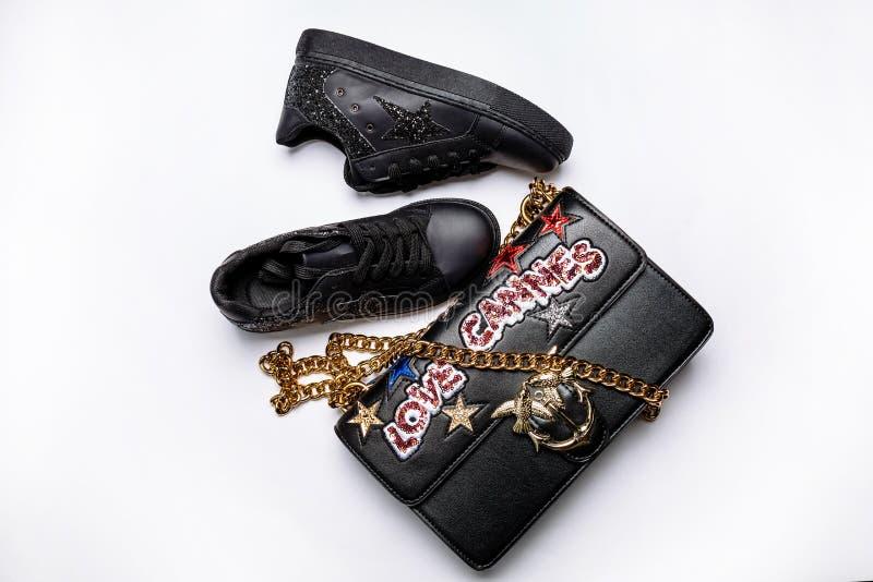 De zwarte tennisschoenen versierden met een ster van zwarte fonkelingen en een zwarte zak met een gouden die ketting met glanzend royalty-vrije stock foto