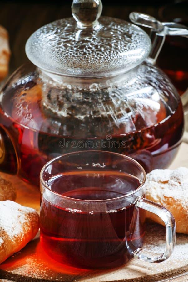 De zwarte thee van Ceylon in glaskoppen met ketel, verse croissants, vi royalty-vrije stock foto's