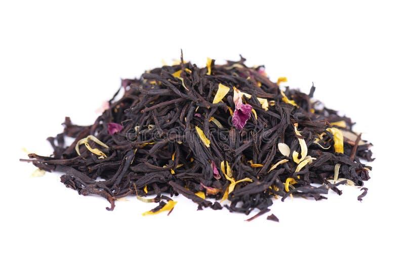 De zwarte thee van Ceylon met roze die bloemblaadjes, korenbloemen, zonnebloem en amandelplakken, op witte achtergrond worden geï stock fotografie