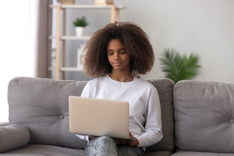 De zwarte tiener zit op laag gebruikend laptop stock foto