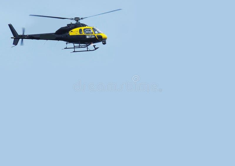 De zwarte van de helikopterbijl met blauwe hemelachtergrond voor het exemplaar van de redacteurstekst stock fotografie