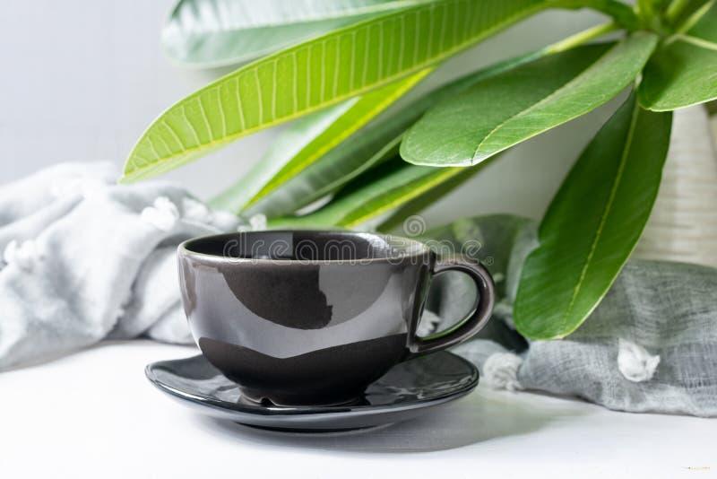 De zwarte van de koffiemok met bladeren op witte houten lijst royalty-vrije stock fotografie