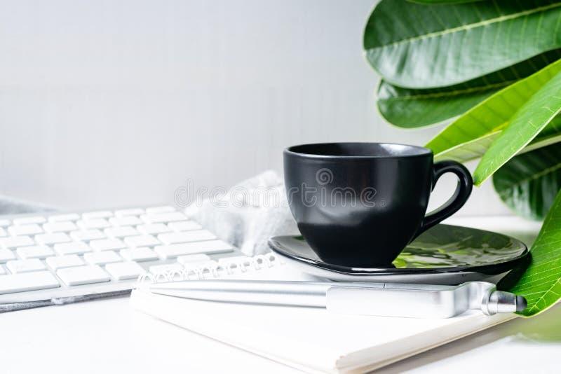 De zwarte van de koffiemok met bloem en bladeren op werkruimte stock fotografie