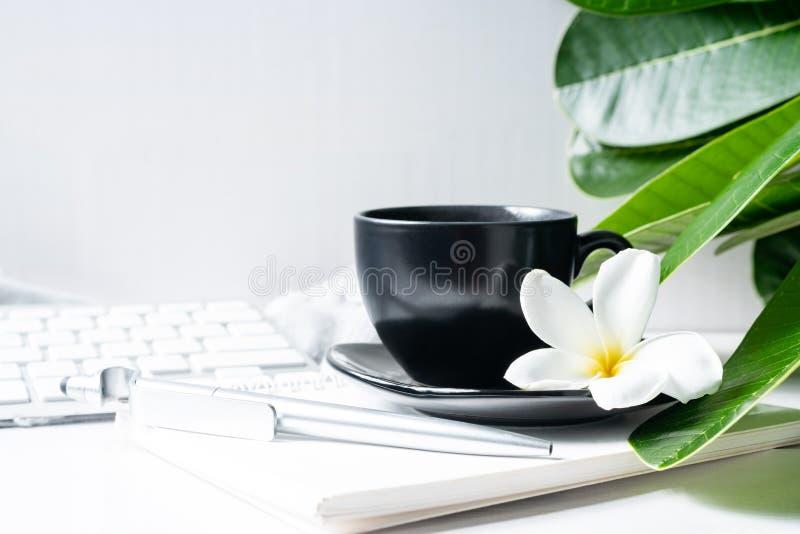 De zwarte van de koffiemok met bloem en bladeren op werkruimte royalty-vrije stock fotografie
