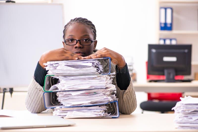 De zwarte vrouwelijke werknemer ongelukkig met het bovenmatige werk stock afbeelding