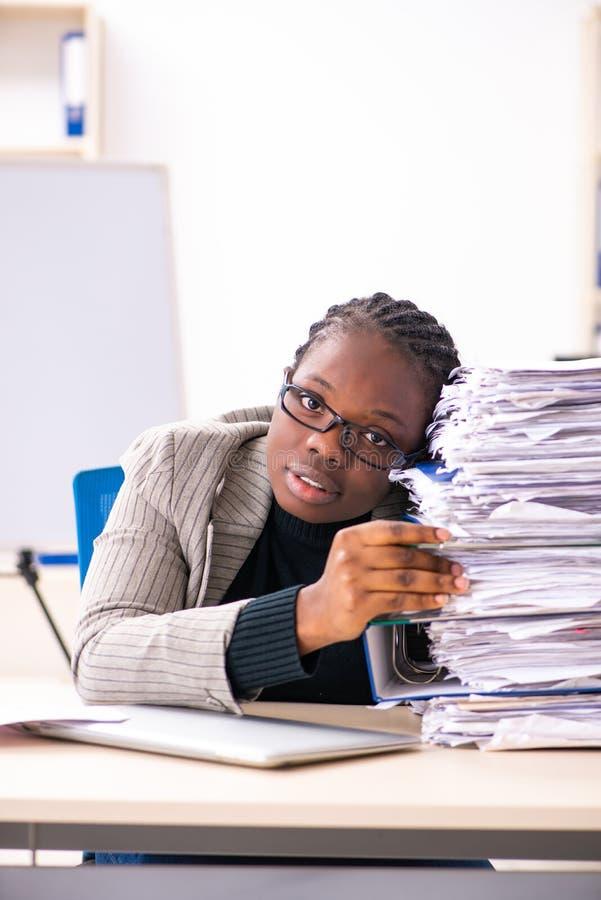 De zwarte vrouwelijke werknemer ongelukkig met het bovenmatige werk stock afbeeldingen