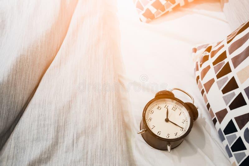 De zwarte wekker op het bed met ochtendzon glanst stock foto's