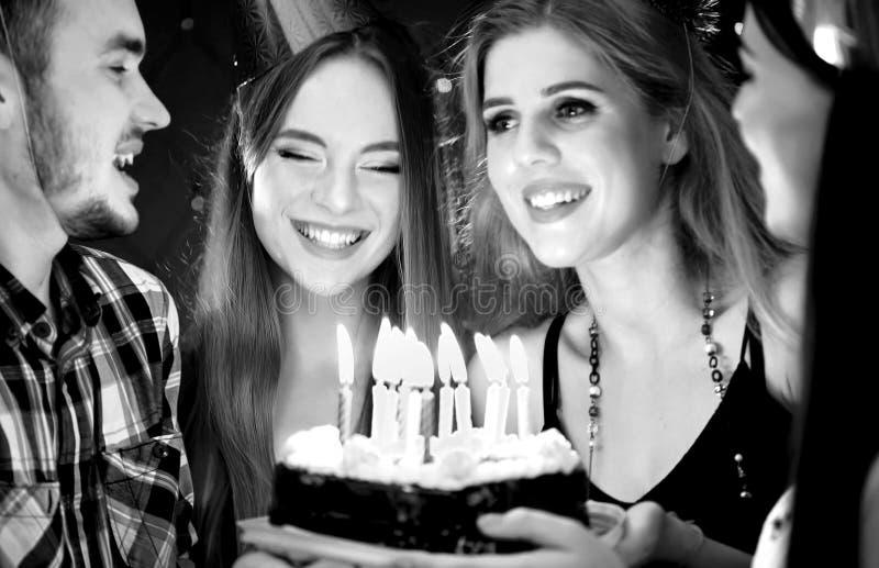 De zwarte witte beelden van de gelukkige partij van de vriendenverjaardag schouwen cakes royalty-vrije stock afbeeldingen