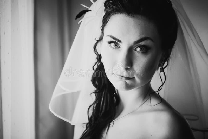 De zwarte witte kosten van de fotografie mooie jonge bruid over modieus venster royalty-vrije stock afbeeldingen