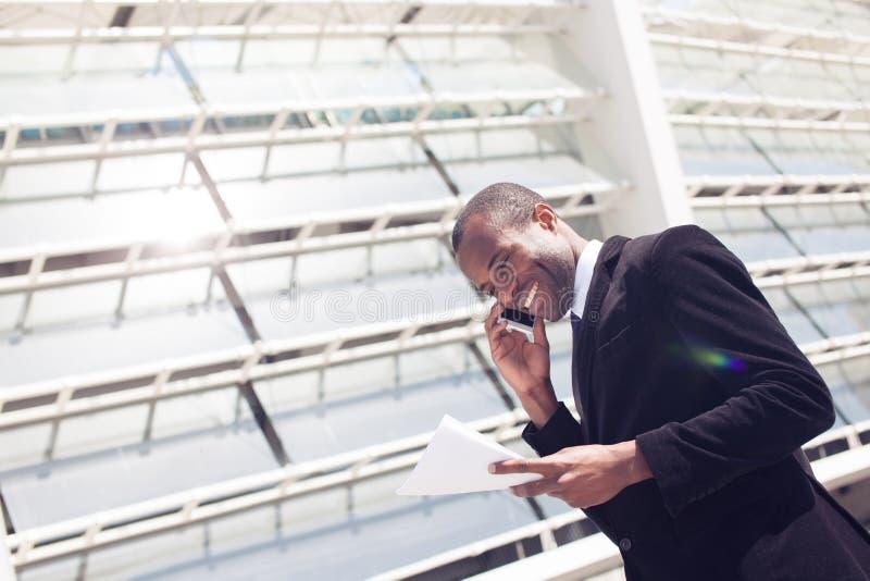 De zwarte zakenman heeft telefoongesprek stock afbeeldingen