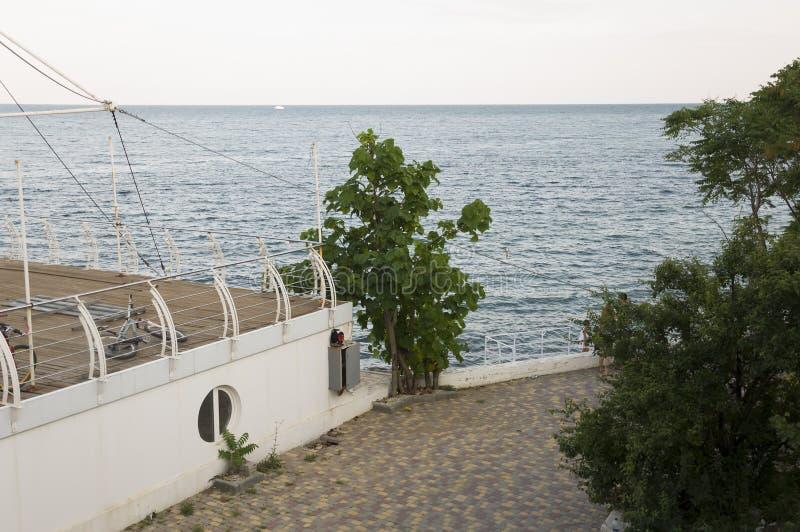 De Zwarte Zee Water zonder golven en weinig boot ver weg rust Bewolkt hoofdzakelijk weer Blauwe en grijze kleur Vóór regen royalty-vrije stock afbeelding