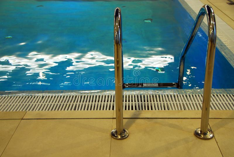 De zwembadladder bij ontspant obiect stock afbeelding